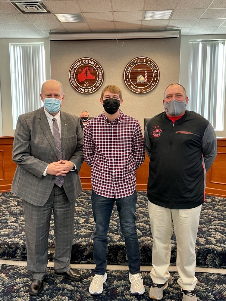 image of Maddox Reynolds with the superintendent and track coach